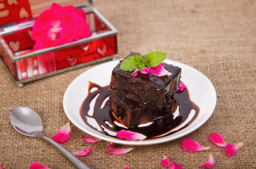 Chocolate brownie on plate with rose petals