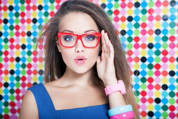 Surprised young woman wearing glasses on spotted background