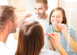 Fototapety Young couple in the bathroom brushing teeth together