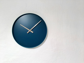 Blue clock on white wall