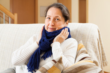 unwell woman in scarf sitting at home