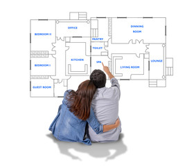 Young couple imaging new house blueprints and planning