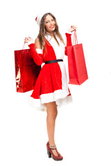 Woman wearing Santa Claus costume holding shopping bags