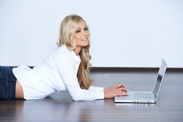 Young woman lying on the floor with a laptop