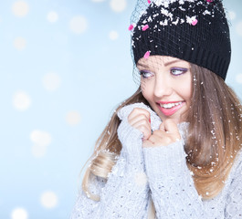 Winter portrait of  woman wearing hat covered with snowflakes