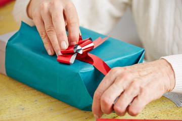 Seniorin verpackt Geschenk mit Schleife zu Weihnachten