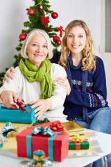 Frau mit Seniorin zu Weihnachten mit Geschenk