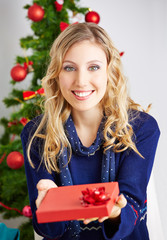 Frau überreicht Geschenk an Weihnachten