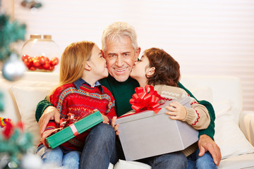 Kinder küssen Opa auf die Wange an Weihnachten