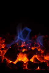 Closeup of glowing hot red embers and blue flame in fireplace