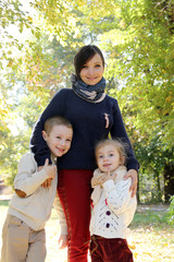 Mother with two kids in autumn park