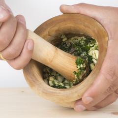 Detalle del cocinero usando el mortero con ajo y perejil