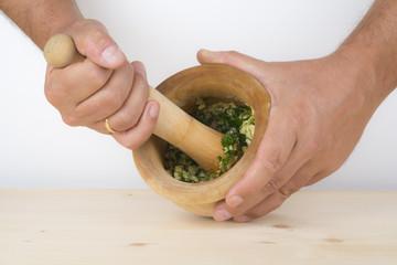 Cocinero preparando un majado de ajo y perejil en el mortero