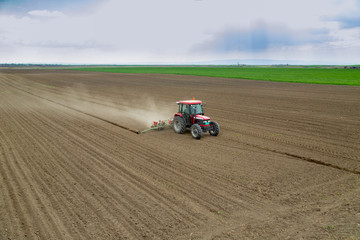 Farmer sowing crops at field with tractor