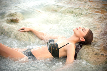 Pretty young woman takes a bath in the natural thermal waters of