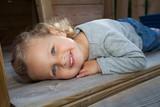 kleines Kind liegt auf einem Spieltrum und ruht sich aus poster
