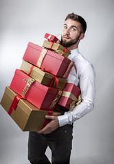 Attraktiver Mann mit vielen Geschenken im Arm