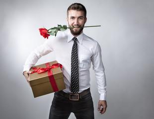Attraktiver Mann mit Geschenk und Rose