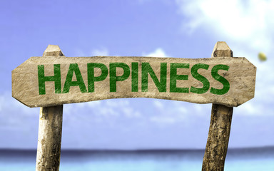Happiness wooden sign with a beach on background