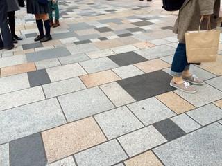歩道に立ち止まる人々の足元