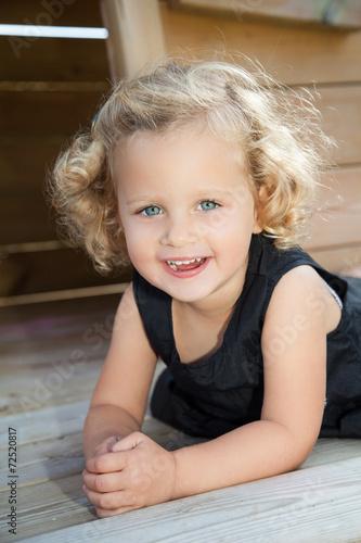 canvas print picture kleines Kind liegt auf einem Spieltrum und ruht sich aus