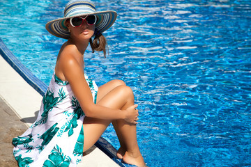woman with sunglasses relax at luxury pool side