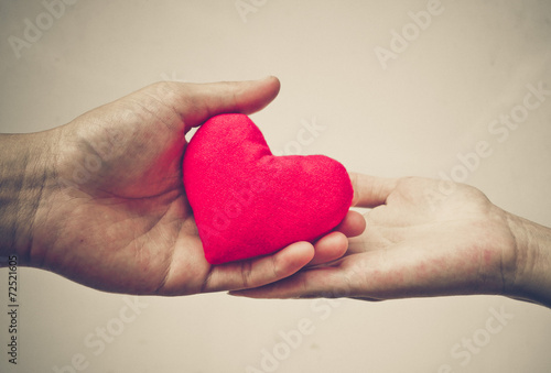 man's hand and woman's hand holding a red heart