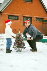 Grandfather and grandson  decorate a Christmas tree
