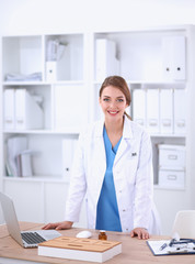 Portrait of happy successful young female doctor holding a