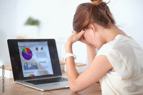 Portrait of tired young business woman with laptop computer at - 72521814