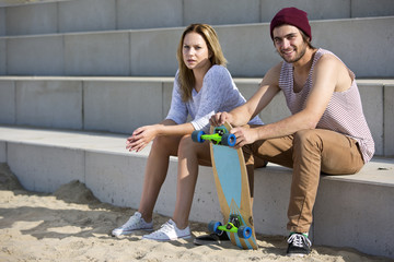 Young skateboarding couple on a beach