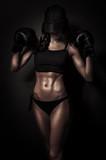 Fit boxing woman in training on black background