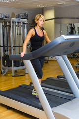Young woman at the gym exercising. Walking  on on a machine