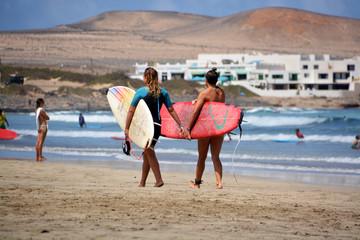 dos surfistas caminando por la playa