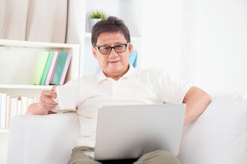 Mature Asian man surfing internet