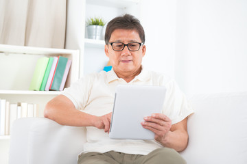 Mature Asian man using tablet pc