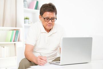 Mature Asian man using computer
