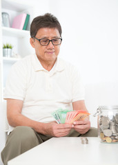 Mature Asian man counting money