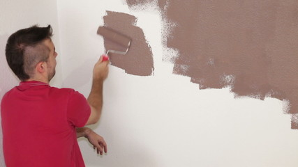 Man with paint roller painting interior