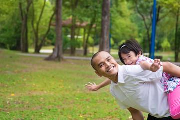 Muslim father and daughter piggyback