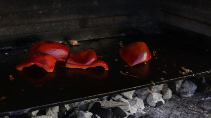 Grilling red Bell Peppers on barbecue grill.