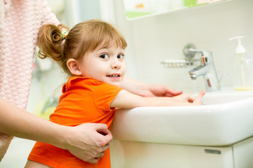 kid girl washing hands with mom help