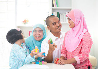 Malay family at home. Muslim girl building a wooden toy house. S