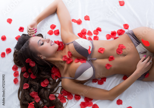 Dreamy model luxuriating on sheet with rose petals - 72529092