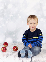 Little boy sitting on the floor with christmas balls
