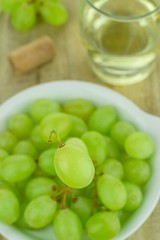 Selective focus of a single grape over a bowl of grapes