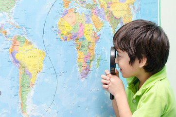 Little boy using magnify looking on map