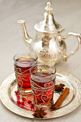 Traditional arabic tea with metal teapot and glasses vertical