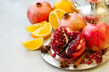 Ripe fruits pomegranate and orange on a silver plate