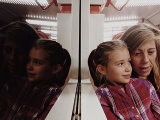 Mother and daughter reflected in a train mirror